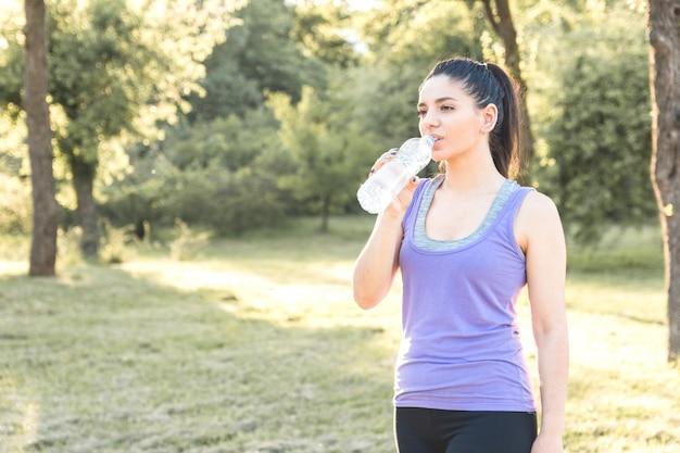 Jovem mulher água potável após treino, se sentindo bem. estilo de vida ativo.