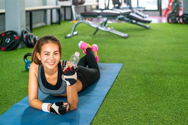 Jovem mulher água potável durante treino no ginásio