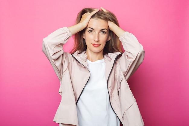 Jovem mulher ajeita o cabelo com uma jaqueta rosa, fundo rosa isolado.