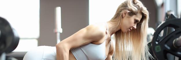 Jovem mulher ajoelhada e levantando halteres no conceito de musculação feminina na academia