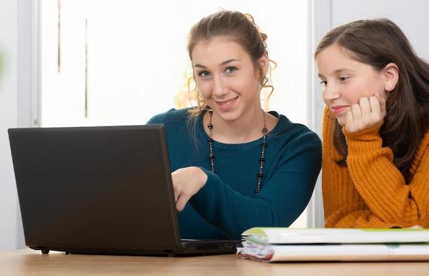 Jovem mulher ajuda uma menina adolescente com lição de casa