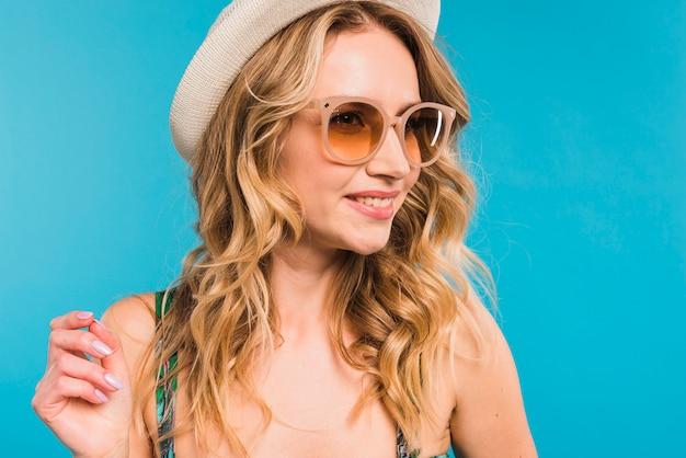 Jovem mulher alegre atrativa no chapéu e nos óculos de sol