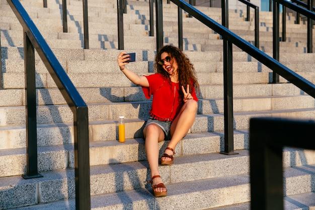 Jovem mulher alegre atrativa que mostra um gesto da paz durante a tomada de um selfie