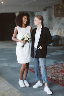 Jovem mulher alegre com cabelo loiro em uma jaqueta preta e sorridente mulher afro-americana com cabelo escuro encaracolado em um vestido branco com flores na mão, olhando um para o outro felizmente na cerimônia de casamento