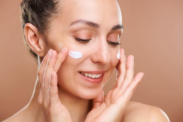 Jovem mulher alegre com um sorriso dentuço, aplicando creme facial rejuvenescedor nas bochechas enquanto cuida da pele pela manhã