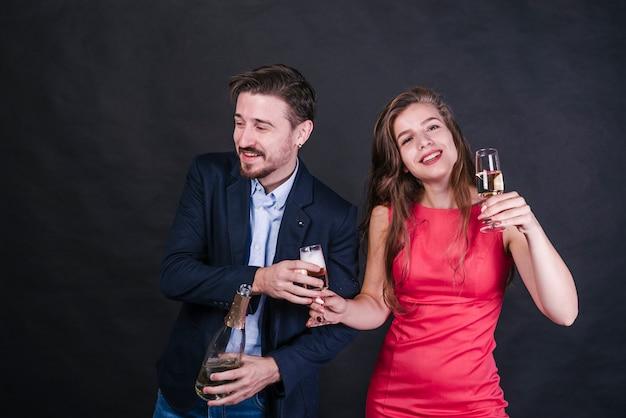 Jovem mulher alegre dando copo de bebida para homem com garrafa de champanhe