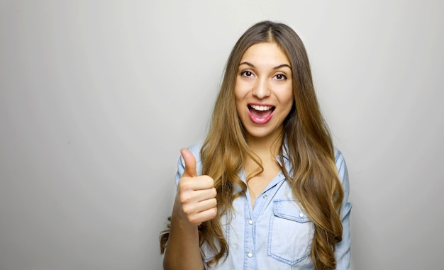 Jovem mulher alegre e feliz mostrando o polegar