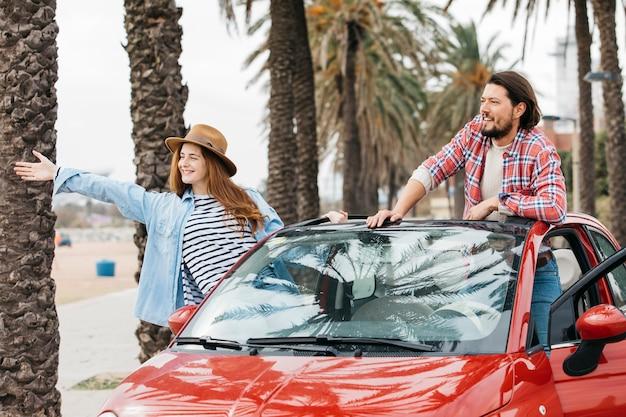 Jovem mulher alegre e homem, inclinando-se para fora do carro
