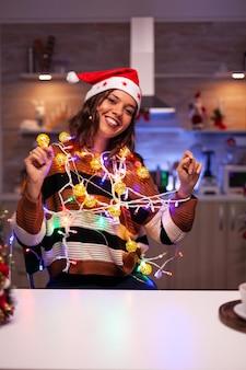 Jovem mulher alegre emaranhada em luzes de cordas