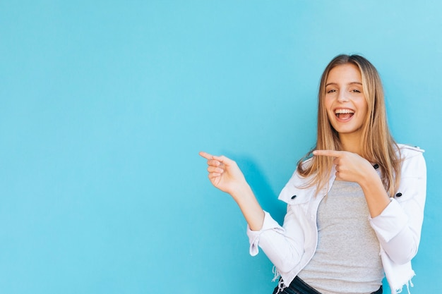 Jovem mulher alegre que aponta seus dedos contra o fundo azul