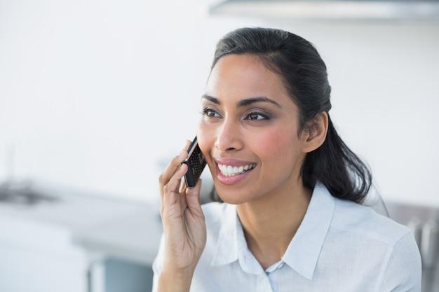 Jovem mulher alegre que telefona com seu smartphone