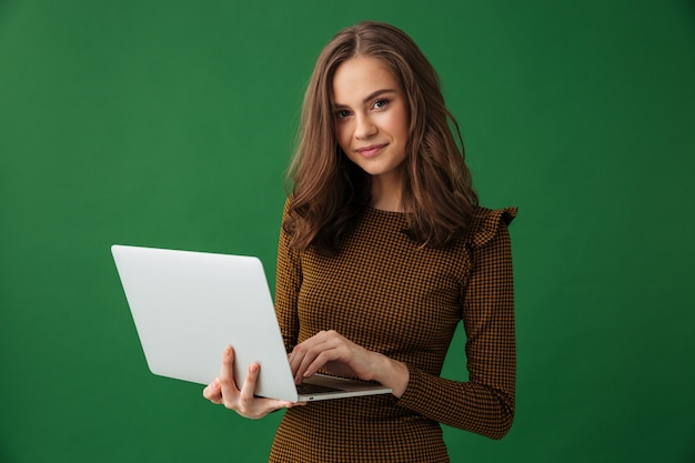 Jovem mulher alegre segurando o computador portátil.