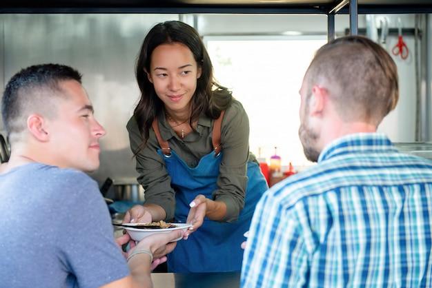 Jovem, mulher, alimento, caminhão, proprietário negócio, comida serve, para, um, cliente