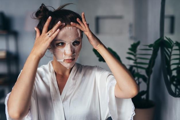 Jovem mulher alisando uma máscara de lençol no rosto.