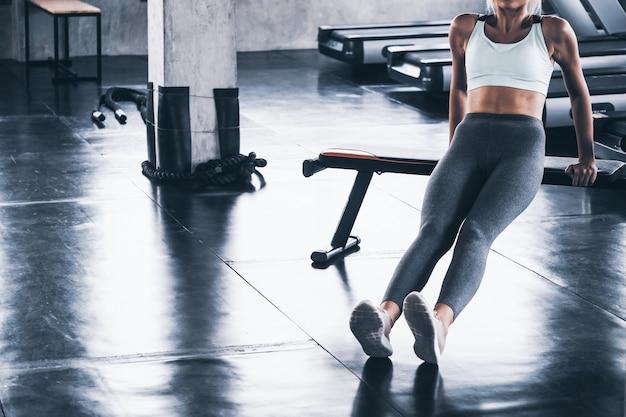 Jovem mulher alongamento e aquecimento antes de treino no ginásio
