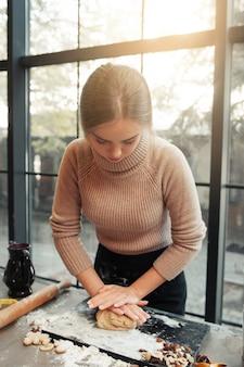Jovem mulher amassar massa na cozinha