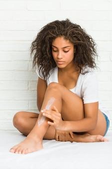 Jovem, mulher americana africana, obtendo, hidratar, creme, ligado, dela, pernas