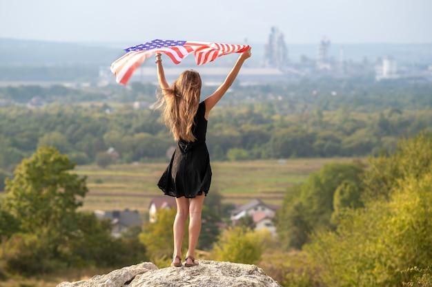 Jovem mulher americana feliz com cabelo comprido, levantando-se acenando no vento a bandeira nacional dos eua nas mãos dela relaxantes ao ar livre, aproveitando o dia quente de verão.
