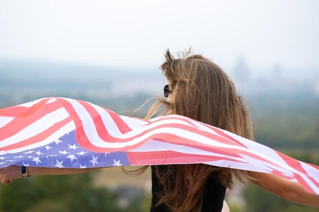 Jovem mulher americana feliz com cabelo comprido, segurando acenando na bandeira nacional dos eua do vento em seus sholders relaxantes ao ar livre, aproveitando o dia quente de verão.