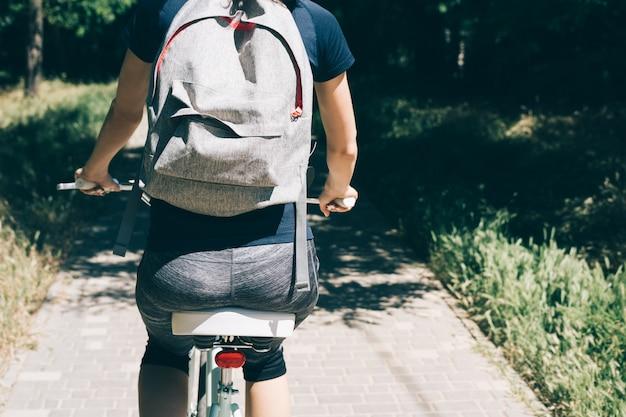 Jovem mulher anda de bicicleta com uma mochila no verão