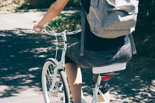 Jovem mulher anda de bicicleta no verão com uma mochila