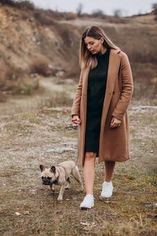 Jovem mulher andando com animal de estimação bulldog no parque