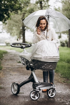 Jovem mulher andando com carrinho de bebê sob o guarda-chuva em um tempo raint