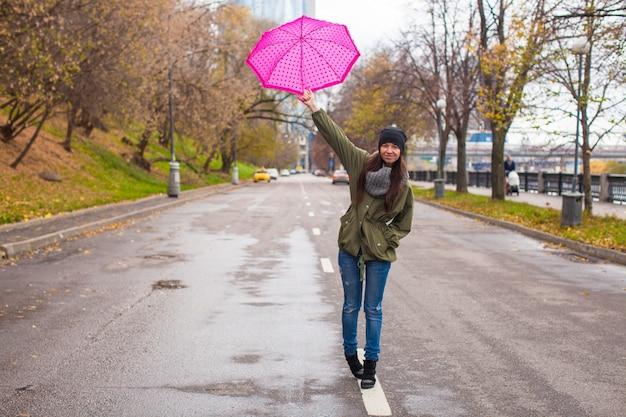 Jovem mulher andando com guarda-chuva no dia chuvoso de outono