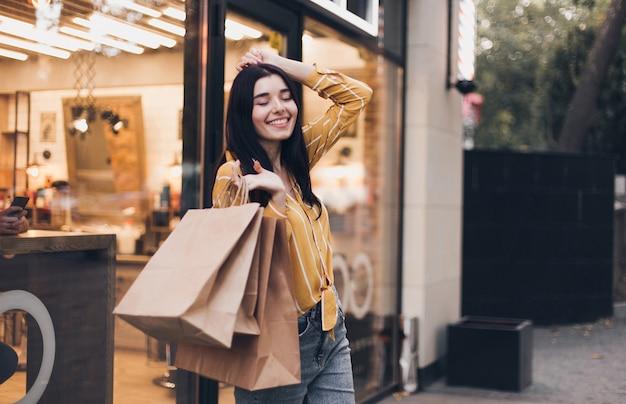 Jovem mulher andando com sacolas de compras na rua da cidade