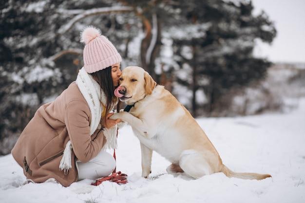 Jovem mulher andando com seu cachorro em um parque de inverno