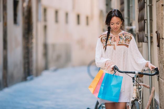 Jovem mulher andando com uma bicicleta e sacolas de compras