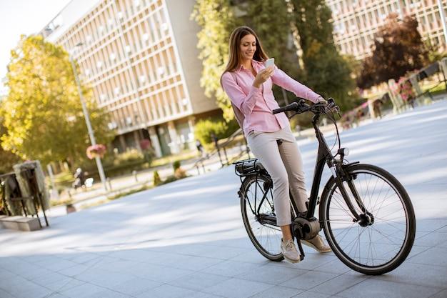 Jovem mulher andando de bicicleta elétrica e usando telefone celular em ambiente urbano