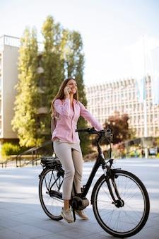 Jovem mulher andando de bicicleta elétrica e usando telefone celular