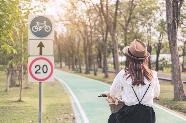 Jovem mulher andando de bicicleta na ciclovia no parque