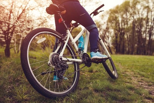 Jovem mulher andando de bicicleta na floresta de primavera. helathy conceito de estilo de vida.