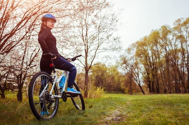 Jovem mulher andando de bicicleta na floresta de primavera.