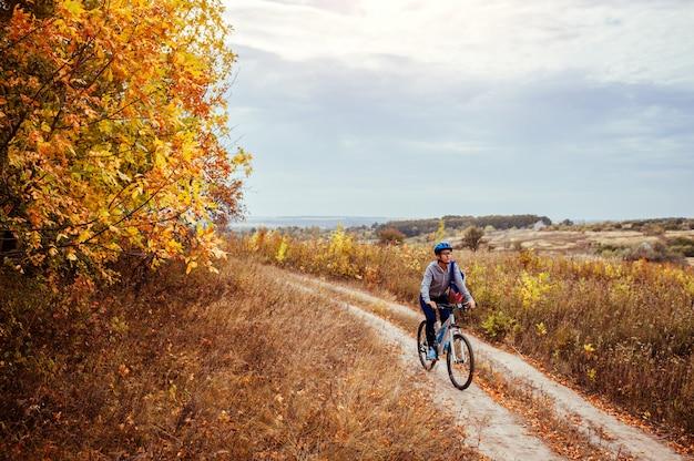 Jovem mulher andando de bicicleta no campo de outono