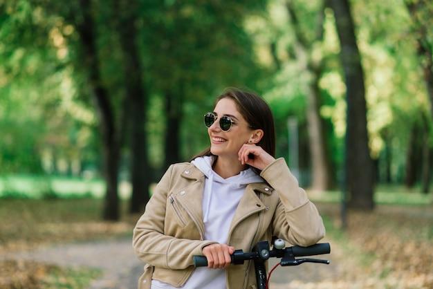 Jovem mulher andando de scooter elétrica em um parque de outono. transporte verde, problemas de congestionamento.