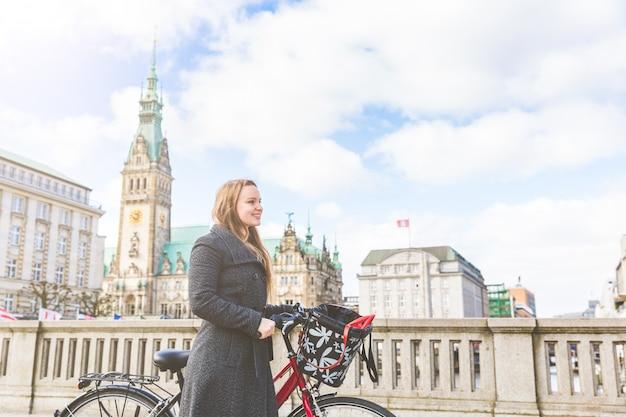 Jovem mulher andando e segurando uma bicicleta em hamburgo