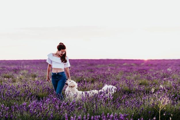 Jovem mulher andando em um campo de lavanda roxo com seu cachorro golden retriever ao pôr do sol. animais de estimação ao ar livre