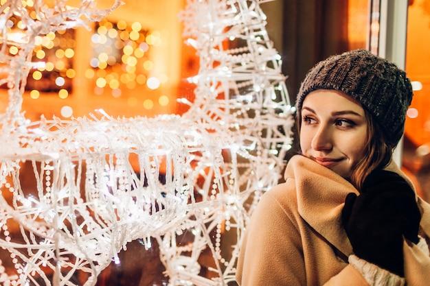 Jovem mulher andando na cidade e olhando vitrines de natal decoradas à noite.