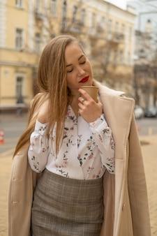 Jovem mulher andando na rua da cidade outono e bebendo tirar café em copo de papel.