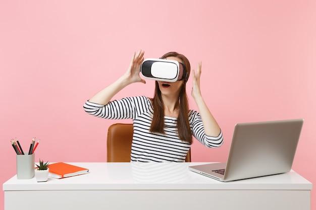 Jovem mulher animada em um fone de ouvido de realidade virtual na cabeça, espalhando as mãos, sentar e trabalhar na mesa branca com o laptop