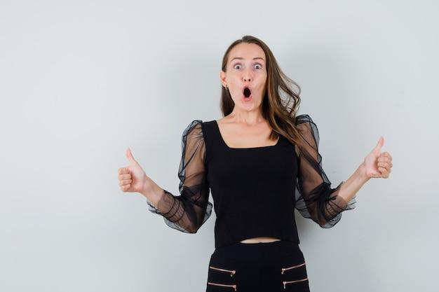 Jovem mulher aparecendo dois polegares para cima em uma blusa preta e calça preta e parece feliz. vista frontal.