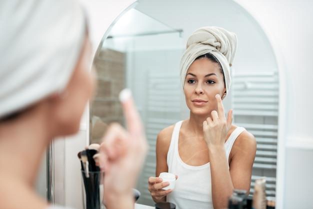 Jovem mulher aplicar creme hidratante no rosto depois de shovering.