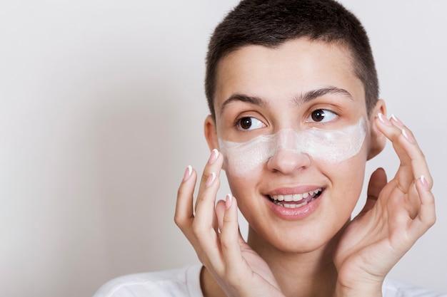 Jovem mulher aplicar creme para o rosto