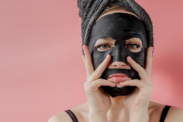 Jovem mulher aplicar máscara facial de tecido cosmético preto sobre fundo rosa. máscara de peeling facial com carvão, tratamento de beleza spa, cuidados com a pele, cosmetologia. fechar-se