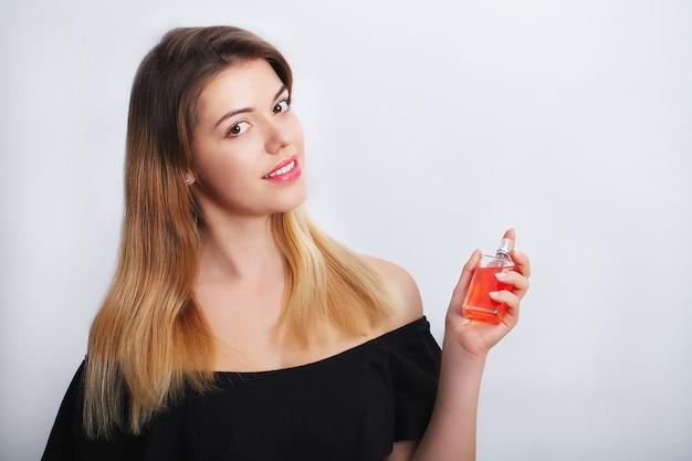 Jovem mulher aplicar perfume no espaço do pescoço para texto