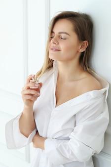 Jovem mulher aplicar perfume.