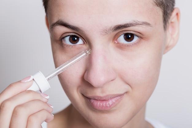 Jovem mulher aplicar produto de cuidados do rosto